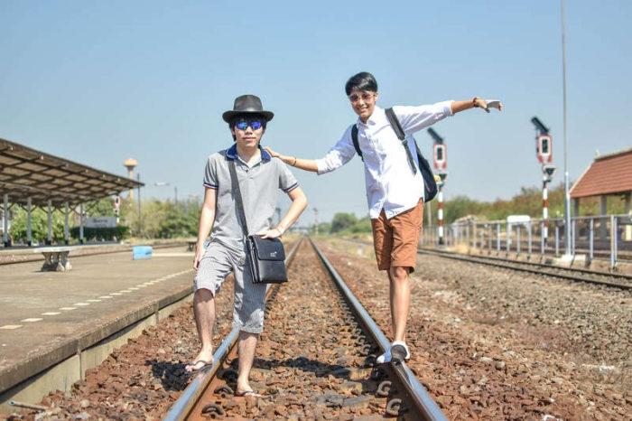 Twee toeristen op een spoorwegovergang in Thailand.