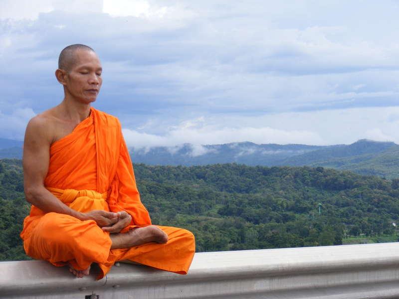 Een thaise monnik, mediterend op een randje zittend met een prachtig landschap achter hem.