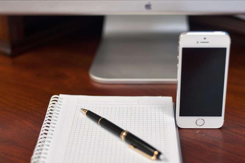 Een afbeelding van een kladblok en een smartphone. Met deze foto word bedoeld dat je een reisdagboek bij kan houden op de ouderwetse manier, met pen en papier, maar dat dit tegenwoordig ook prima op de mobiel te doen is.