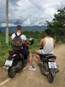 een van achter genomen foto van twee jong volwassen op een scooter in de noordelijk gelegen bergen van Thailand