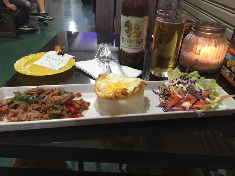 Foto van een authentiek Thais gerecht: Fried basil and pork. Daarnaast staat er een heerlijk Thaise biertje op tafel.