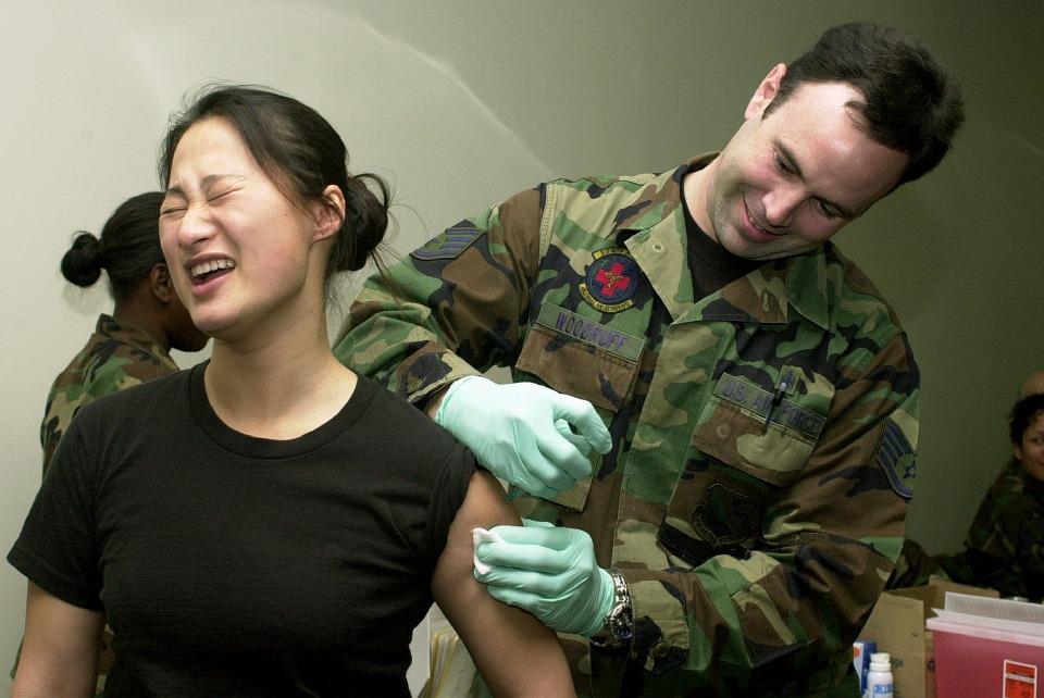 Een Aziatische vrouw die een inenting krijgt toegediend.