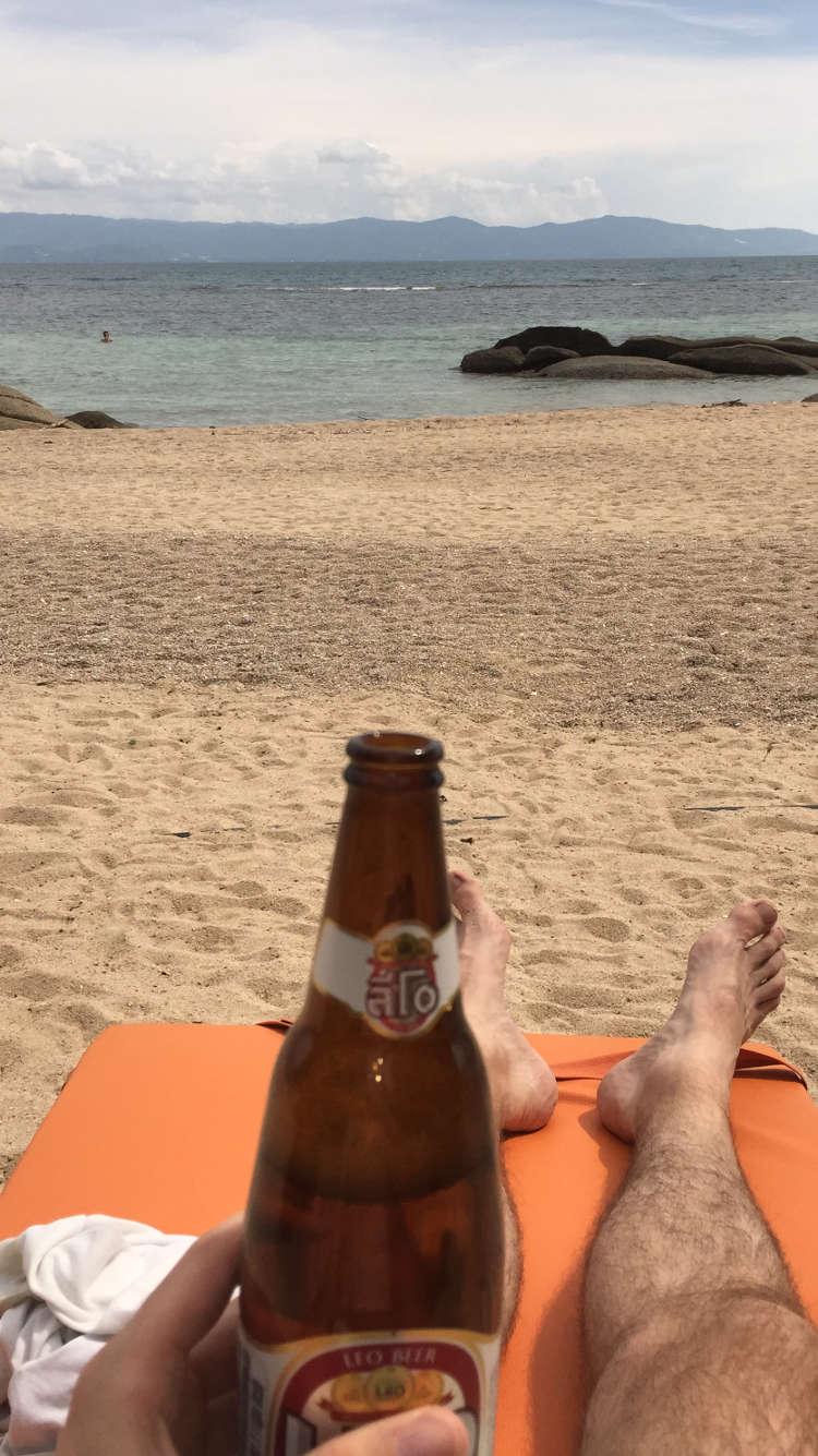 Foto van iemand die heerlijk op het strand geniet van een biertje