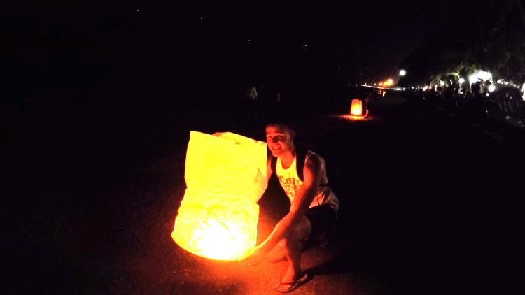 Foto waarop een backpacker een lantaarn loslaat ter viering van het Loy Kratong festival in Thailand