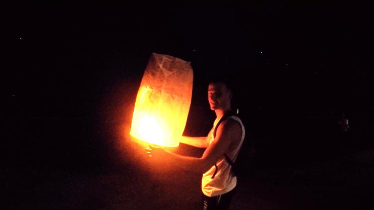 Foto waarop een backpacker zijn lantaarn loslaat ter viering van het Loy Krathong festival in Thailand