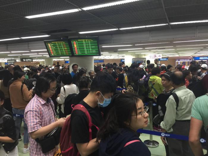 Afbeelding van een lange wachtrij voor de Thaise immigratie bij Don Muang Internationaal airport
