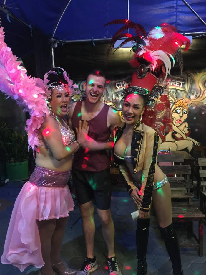 Een foto van een backpacker in Thailand die poseert met twee ladyboys.