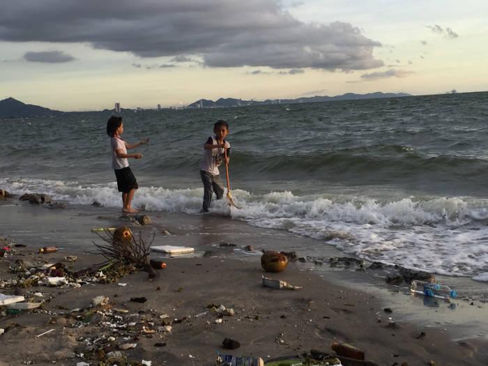 Afbeelding van spelende kinderen die met afval spelen op het strand van Bangsaen.