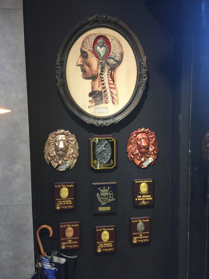 Afbeelding van de prijzen die aan de muur hangen bij BKK ink in Bangkok.