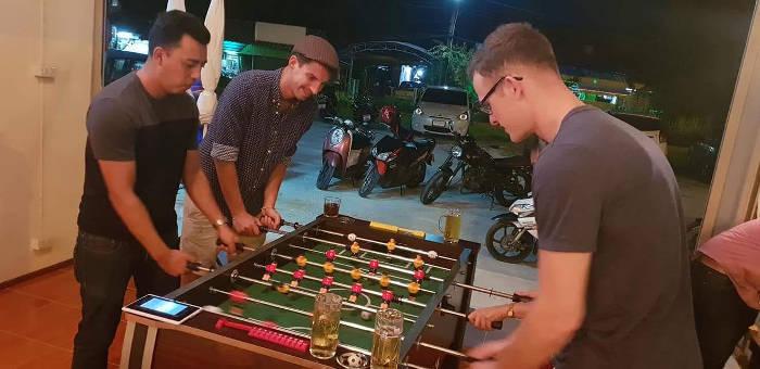 Afbeelding van wat buitenlanders die een potje tafelvoetbal spelen bij de Say Hi corner in Bangsaen, Thailand.