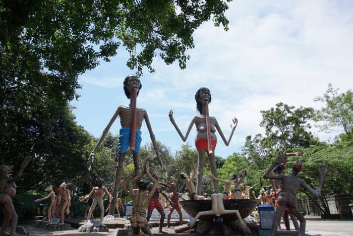 Afbeelding van twee grote beelden in de Wang Saen Suk hell garden in Thailand.