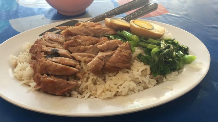 Afbeelding van een bord rijst met stukjes varkensvlees en ei.