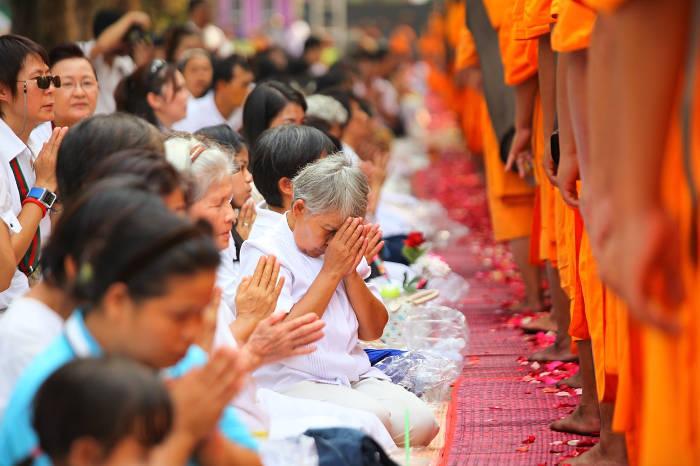 Afbeelding van een oudere mevrouw die een Thaise groet uitvoert naar een monnik,