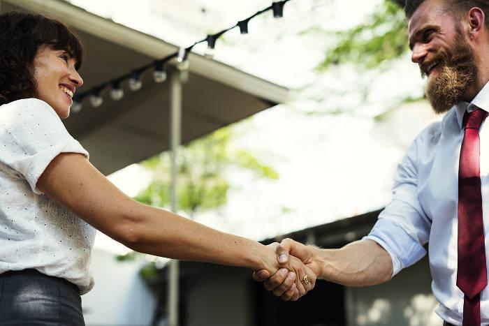 Afbeelding van een meneer en een mevrouw die elkaar een hand geven.