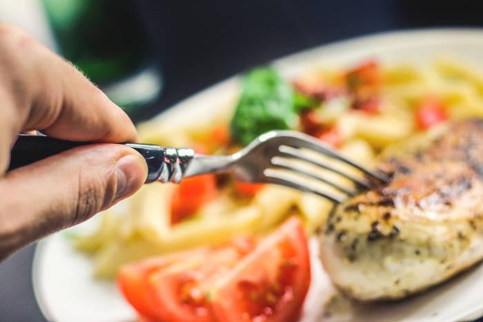 Foto van iemand die met zijn vork in een stuk vlees prikt.