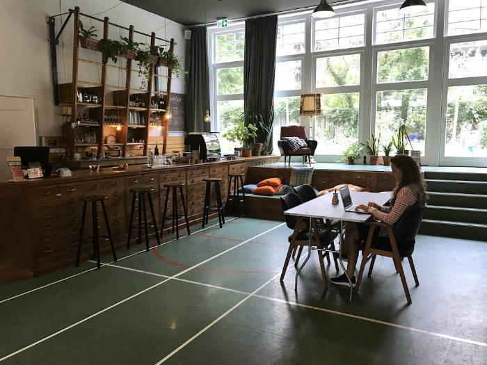 Een foto van Agnes Nederhof die als digital nomad aan het werk is in een co working space in Amsterdam.