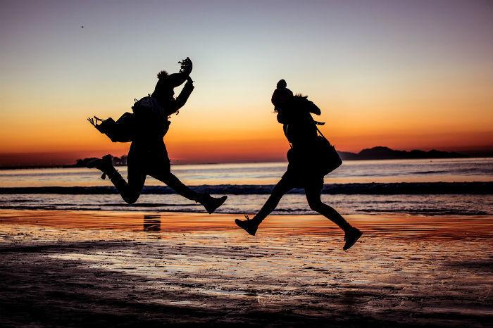 Foto van twee reizigers die op het strand rondspringen en van hun leven genieten.