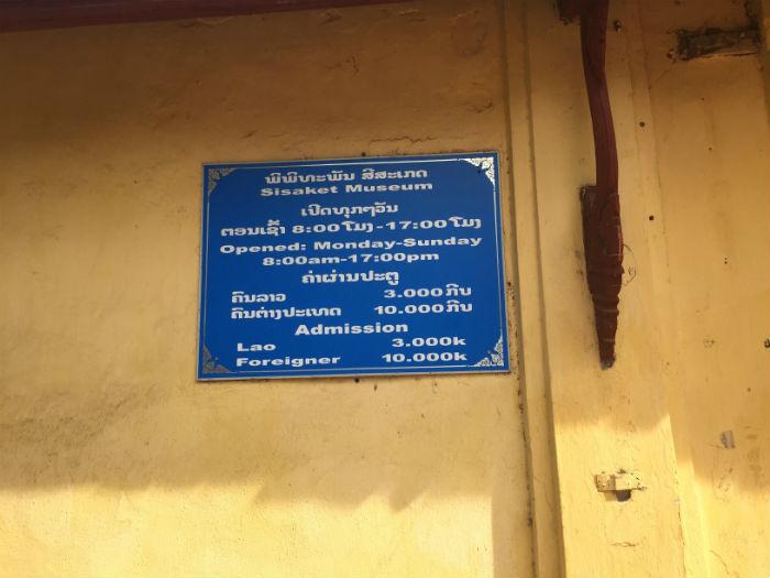 Informatiebord bij de Wat Sisaket tempel waarop de openingstijden en entreekosten vermeld staan.
