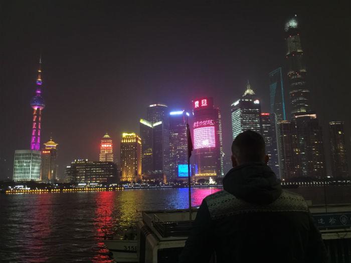 Foto van een reiziger die in de avonduren bij de bund in Shanghai staat.