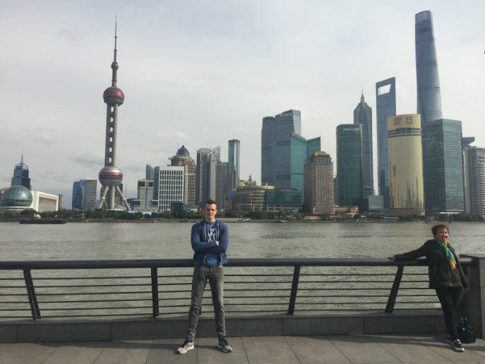 Foto van een reiziger die overdag bij de bund in Shanghai staat.