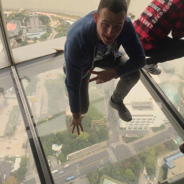 Foto van iemand die op de glazen plaat van de Shanghai Oriental Pearl Tower zit.