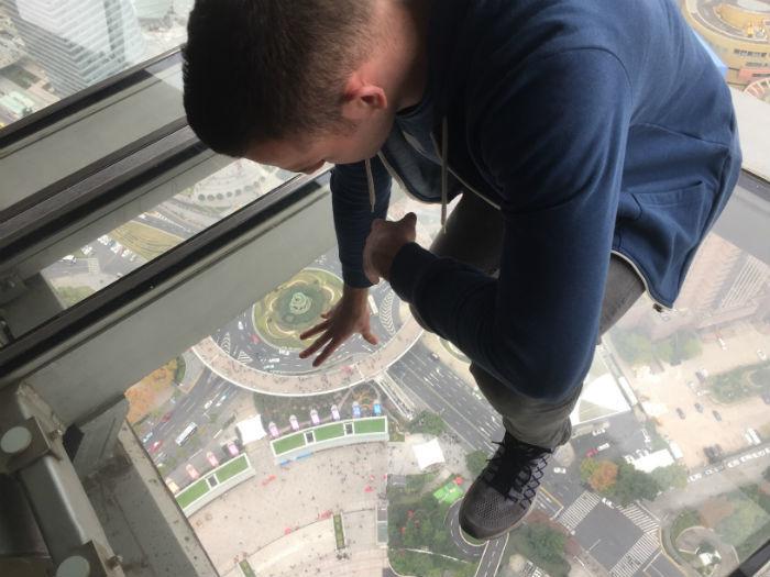 Foto van iemand die gehurkt op de glazen plaat van de Oriental Pearl Tower zit.