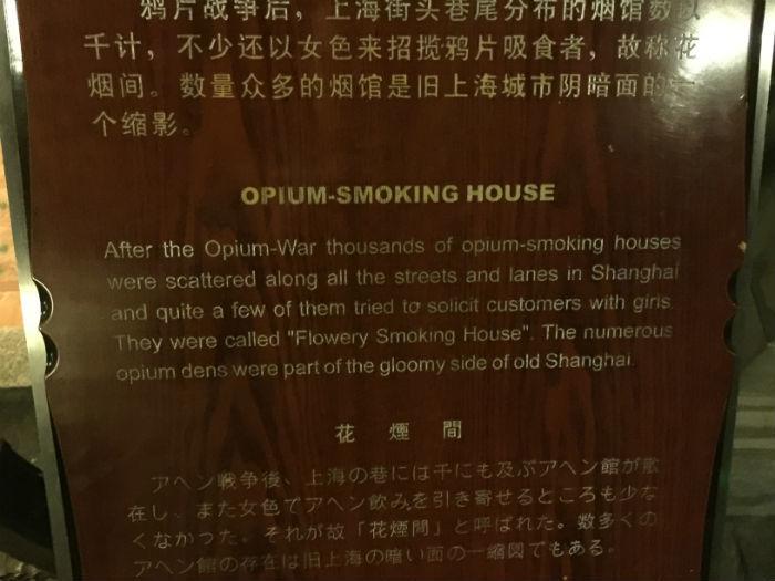 Foto van een informatiebord in het historisch museum van Shanghai  waarop de historie van opium rook huizen in Shanghai beschreven wordt.