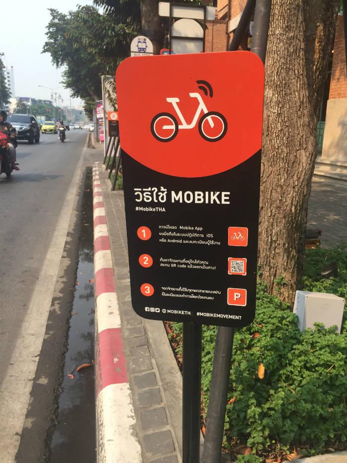 Foto van een informatiebord in Chiang Mai waarop de werking van Mobike wordt uitgelegd.
