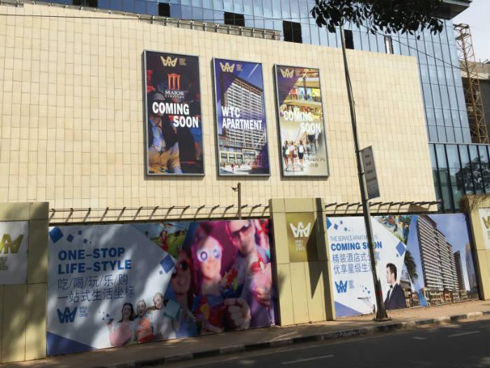 Een foto van flyers op een muur die de bouw van een toekomstig winkelcentrum aankondigen.