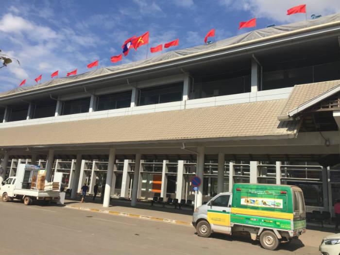 Foto van communistische vlaggen die op het dak van het vliegveld van Vientiane wapperen.
