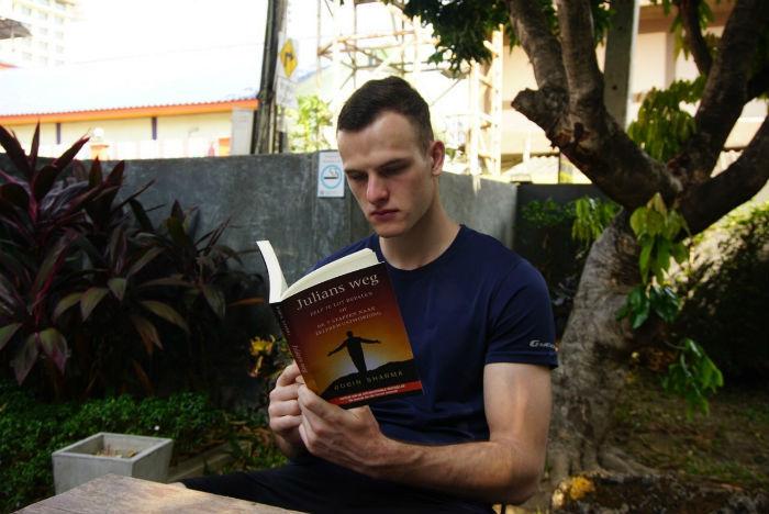 Persoon die het boek Julians weg aan het lezen is.