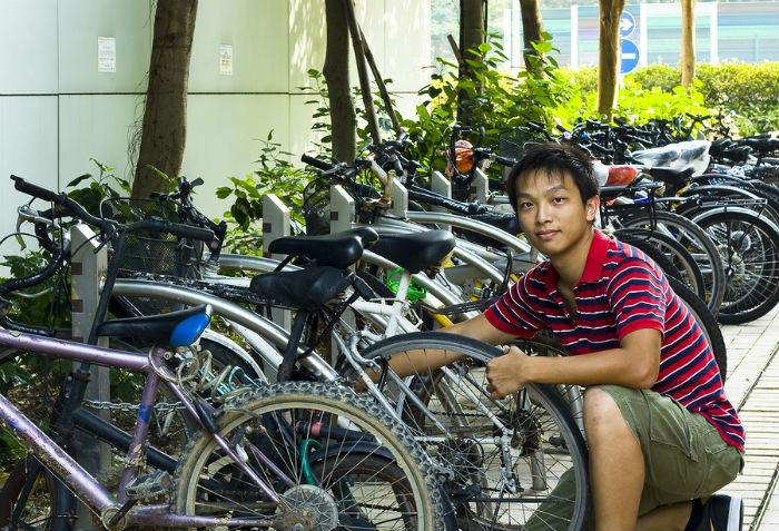 Aziatische jongen repareert fiets